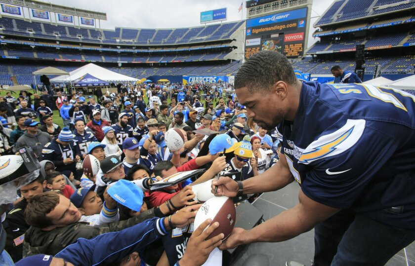 Darrell Stuckey signs autographs for Chargers fans during DraftFest at Qualcomm Stadium.