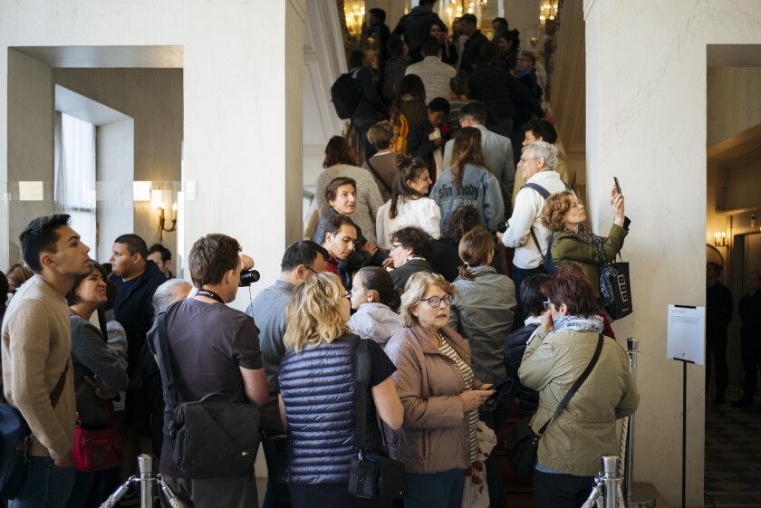 People queue to visit the Elysee Palace, in Paris, Saturday, Sept. 21. 2019. The national buildings and administrations of France are open to the public for the Heritage Days weekend. (AP Photo/Kamil Zihnioglu)