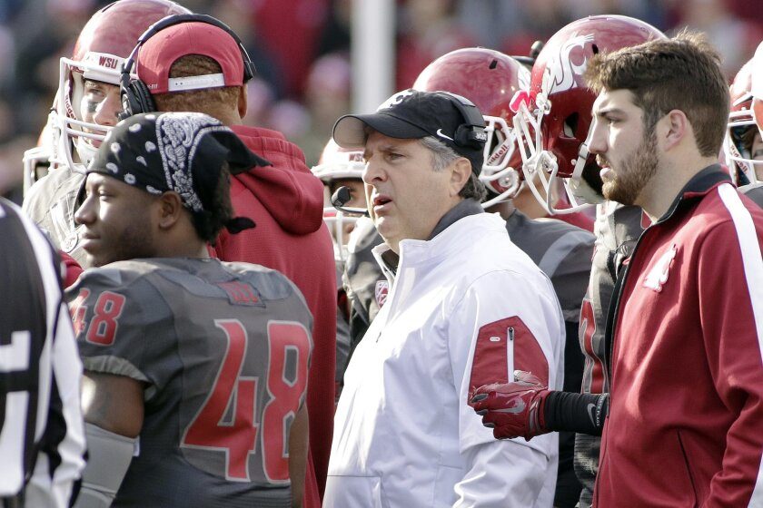 Washington State head coach Mike Leach, center, speaks in the huddle during a timeout in the first half of an NCAA college football game against Arizona State, Saturday, Nov. 7, 2015, in Pullman, Wash. (AP Photo/Young Kwak)