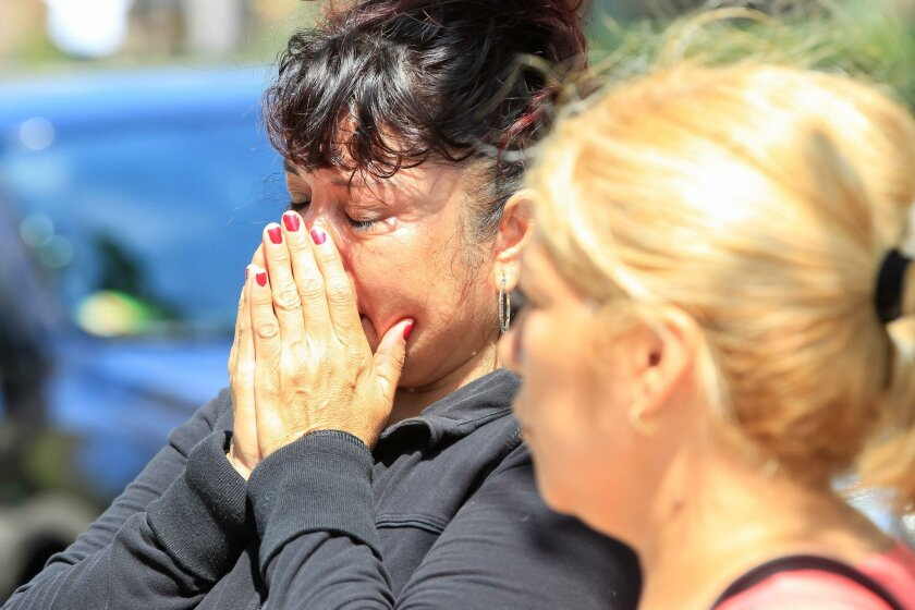 Petra Miranda (left) and Adriana Figueroa break down and cry when they visit the memorial to fallen officers at the San Diego Police Headquarters on Saturday in San Diego.
