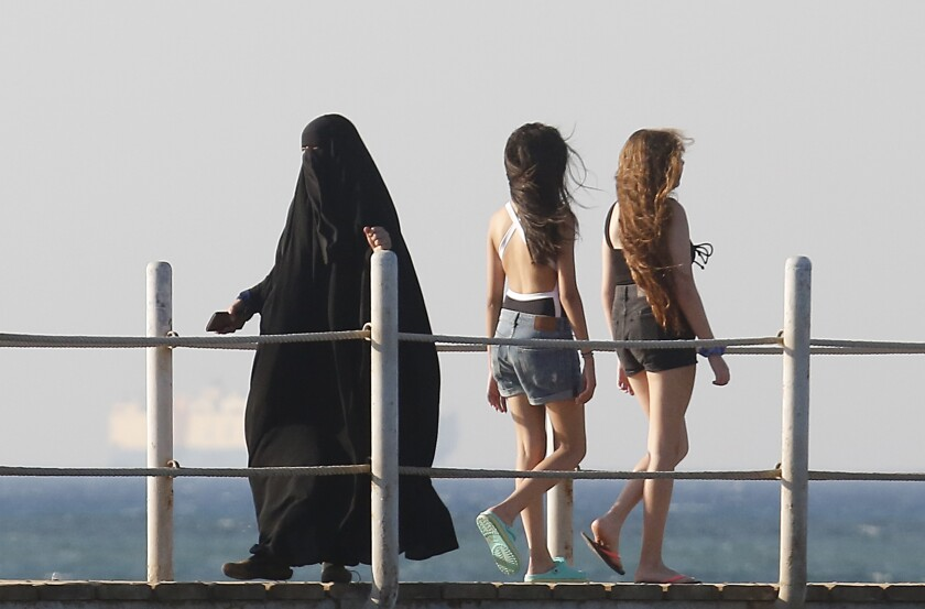 FILE - In this July 26, 2019 file photo, holiday makers walk at al Sokhna beach in Suez, Egypt. The burkini, a swimsuit worn by conservative Muslims to cover the entire body, is scorned in many upper class Egyptian circles where it and the headscarf is seen as lower class. Women who wear the burkini or headscarves can face discrimination in upper-class beach resorts or in bars or clubs, though across Egypt the majority of women wear conservative dress. (AP Photo/Amr Nabil)