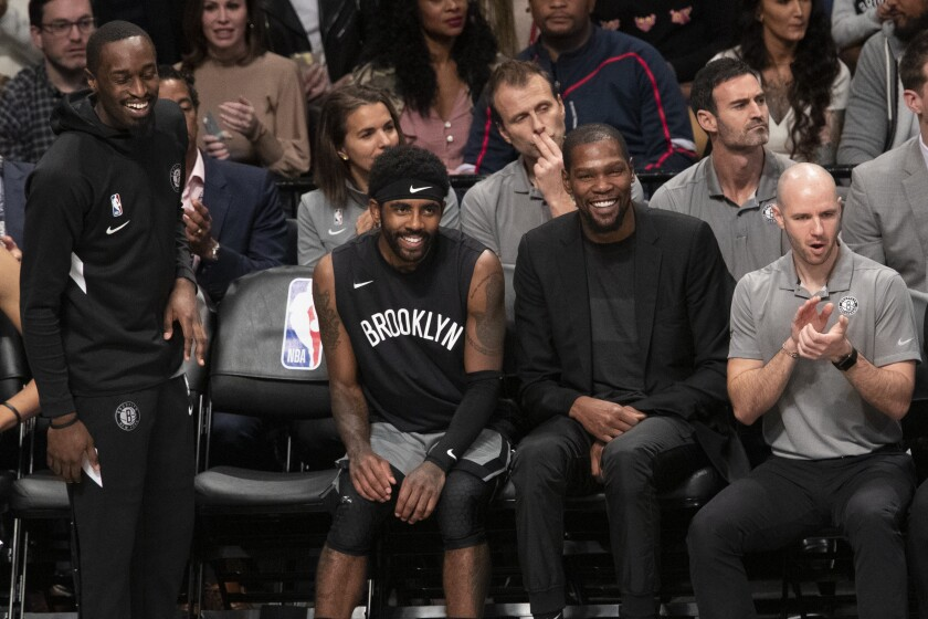 Brooklyn Nets guard Theo Pinson, left, guard Kyrie Irving, center and forward Kevin Durant watch the game action during the second half against the Houston Rockets on Nov. 1, 2019 in New York.