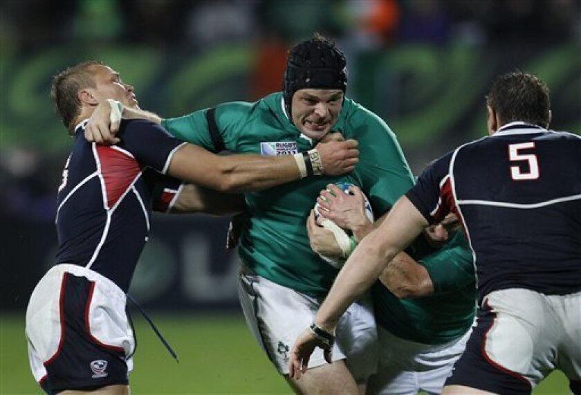 Ireland's Mike Ross, center, attempts to fend of Paul Emerick, left, of the USA and Hayden Smith, right, during their Rugby World Cup game in New Plymouth, New Zealand, Sunday, Sept. 11, 2011.(AP Photo/Dita Alangkara)