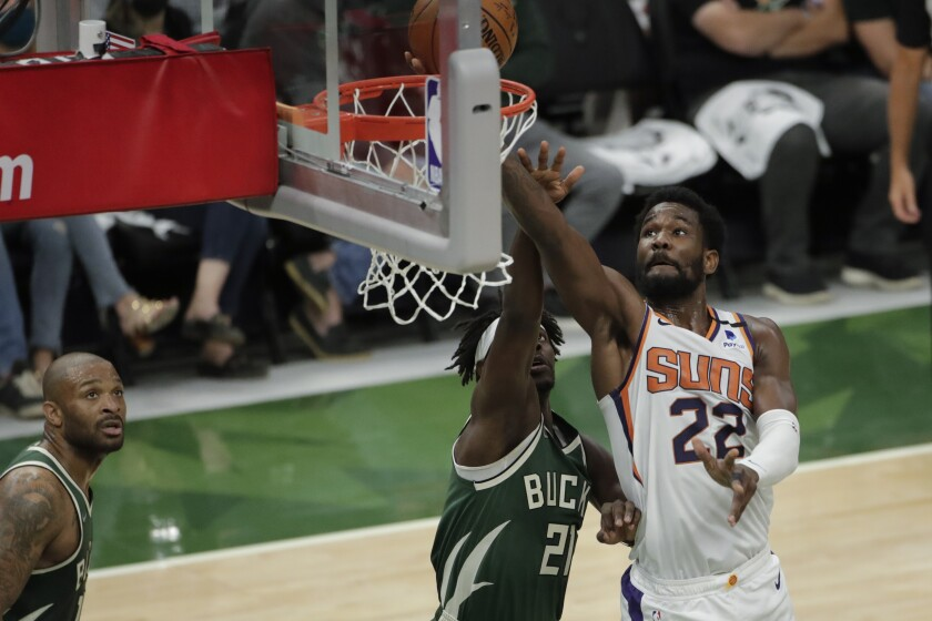Phoenix Suns' Deandre Ayton (22) shoots against Milwaukee Bucks' Jrue Holiday (21) during the first half of Game 3 of basketball's NBA Finals, Sunday, July 11, 2021, in Milwaukee. (AP Photo/Aaron Gash)