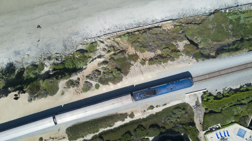 In this August file photo, an Amtrak train makes its way along the Del Mar bluffs that have been plagued by cliff collapses in recent years due to erosion linked to rising ocean levels.