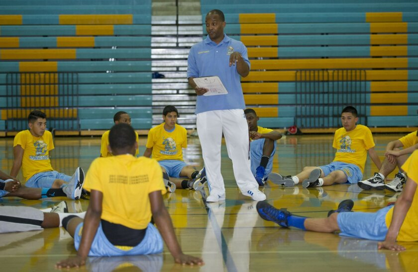 Terry Tucker, athletic director, football coach and basketball coach, talks to members of his summer basketball team.