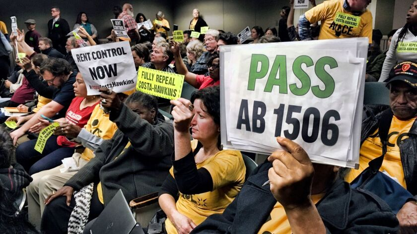 Voters hold signs demonstrating their support for legislation that would allow California communitie