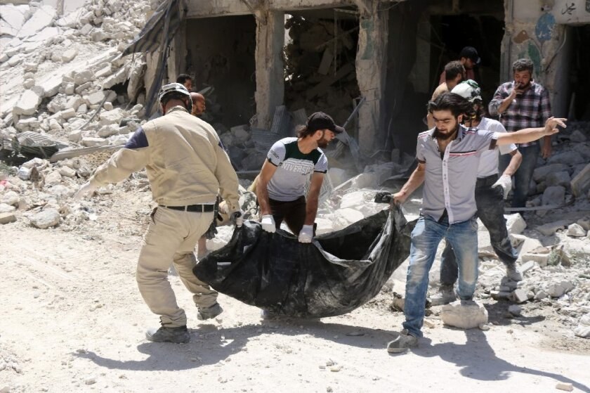Syrian civil defense workers remove a body from the rubble of a building following reported airstrikes on rebel-head areas in Aleppo.