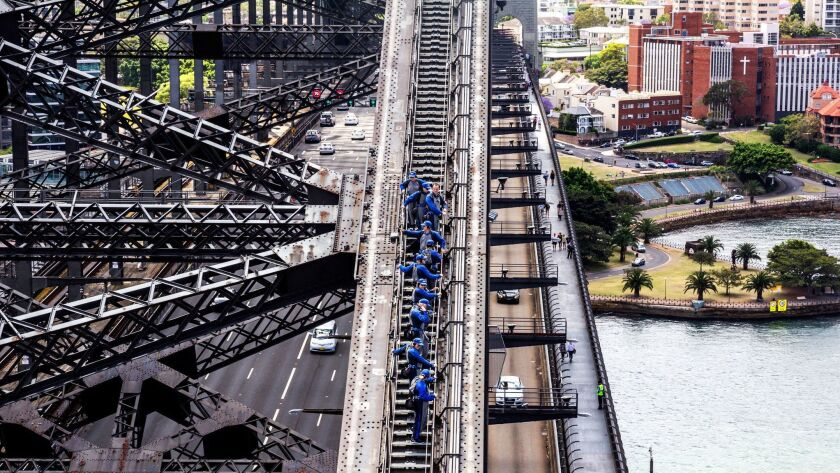 Small groups of people doing the Sydney Harbour Bridge Climb.