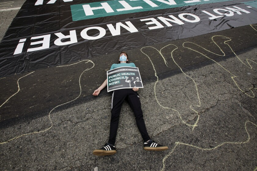 A protester lies on Temple Avenue during a die-in rally by essential workers
