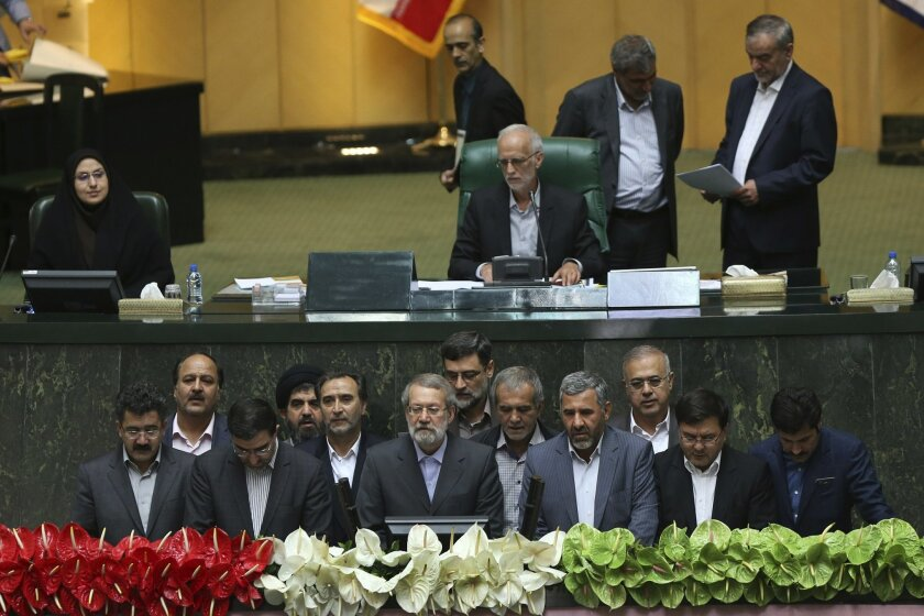 Interim presiding board of Iran's new parliament, bottom, including speaker Ali Larijani, bottom center, take an oath in an open session of the parliament in Tehran, Iran, Sunday, May 29, 2016. Iran's long-serving parliament speaker Larijani will retain his post despite gains by reformists in elect