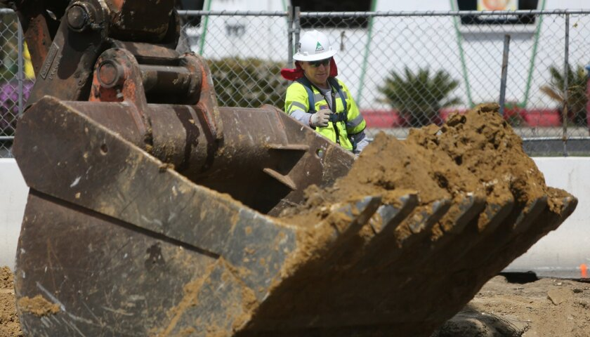 Mike McNulty directs an excavator operator Wednesday in San Marcos, where construction has begun on a 10-mile pipeline that will carry desalinized seawater from the coastal plant being built in Oceanside.