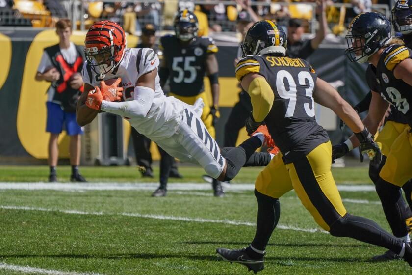 Cincinnati Bengals wide receiver Tyler Boyd (83) dives past Pittsburgh Steelers inside linebacker Joe Schobert (93) for a touchdown during the first half an NFL football game, Sunday, Sept. 26, 2021, in Pittsburgh. (AP Photo/Gene J. Puskar)