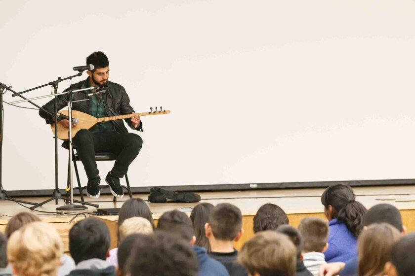 Rodi Yousseff, Syrian refugee and San Diego resident, plays the Baklama, a traditional 7-string Turkish instrument, for Muirlands Middle School eighth-grade students during an author talk on 'They Poured Fire On Us From the Sky.'