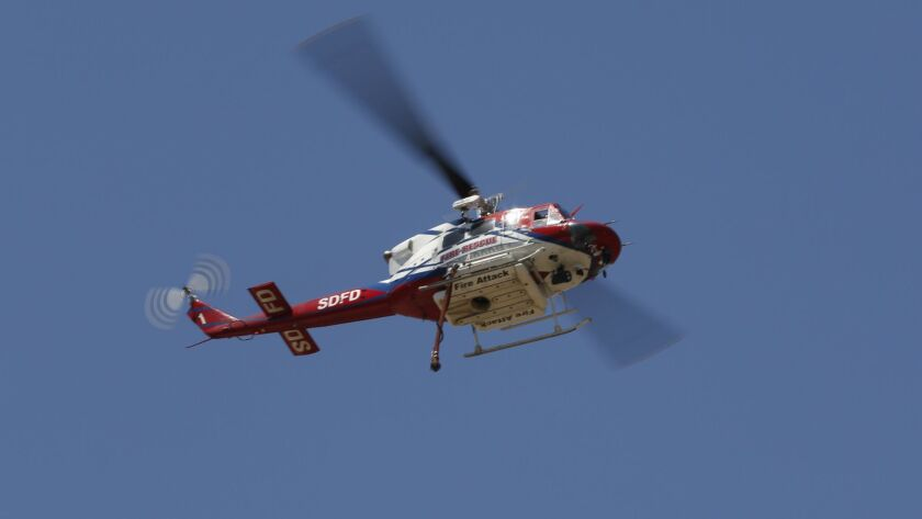 San Diego Fire helicopter stayed in the area as fire fighters on the ground put out a brush fire between Interstate 805 and Miramar National Cemetery.