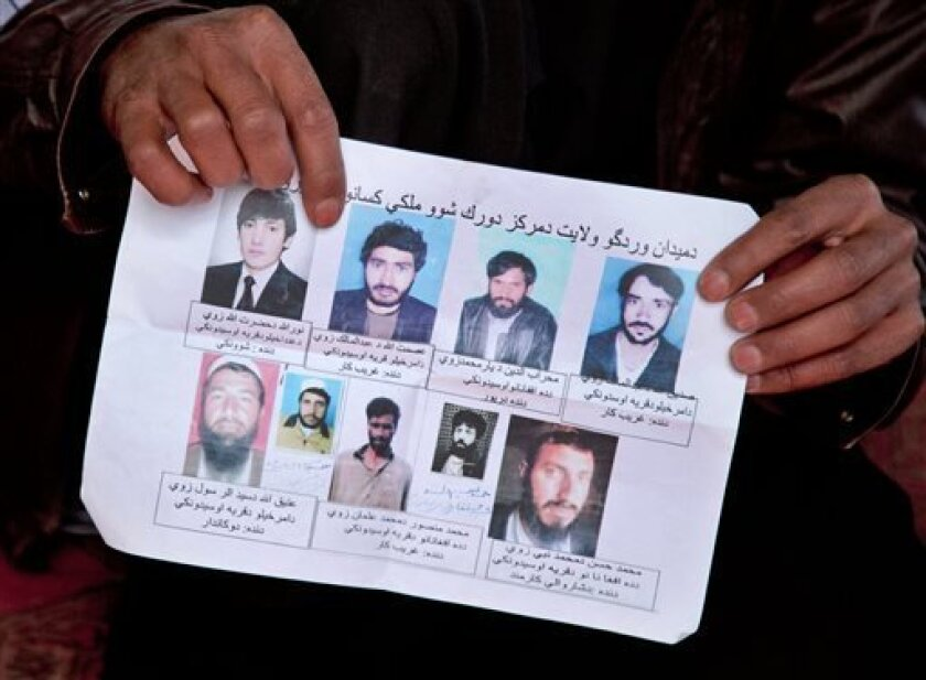 A missing-persons poster, with pictures of nine men who their relatives say were last seen being arrested by U.S. special operations forces, is held by a villager in Maidan Shahr, Afghanistan on Sunday, March 10, 2013. The posters were up for several months, but taken down after the bodies were fou