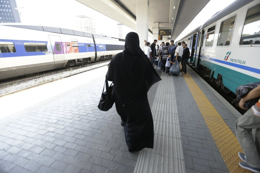 In this picture taken Thursday, June 11, 2014, Syrian refugees arrive at the Garibaldi train station in Milan, Italy. Every day, boatloads of refugees arrive on Italian shores. European Union law requires Italy to fingerprint them, so that if they apply for asylum in another country they can be sent back to their port of entry. Instead, Italy is helping thousands of undocumented migrants slip quietly into northern Europe, with no record of their time in Italy. (AP Photo/Luca Bruno)