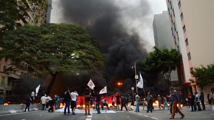 Demonstrators block a roadway in Sao Paulo, Brazil, on Tuesday during a protest against the possible impeachment of Brazilian President Dilma Rousseff. According to official reports, protesters in support of Rousseff blocked 14 highways in 27 Brazilian states to decry the impeachment processes against her.
