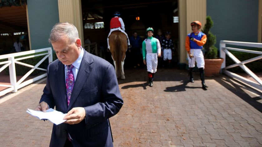 Racetrack executive Tim Ritvo reviews some papers outside the paddock at Santa Anita Park on June 3.