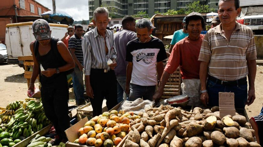 People buy groceries at the municipal market of Coche, a neighborhood of Caracas on Aug. 18.