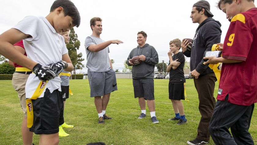 Newport Beach residents Kevin, left, and Nick Marheime as wells as Luca Delancellotti, right, give i