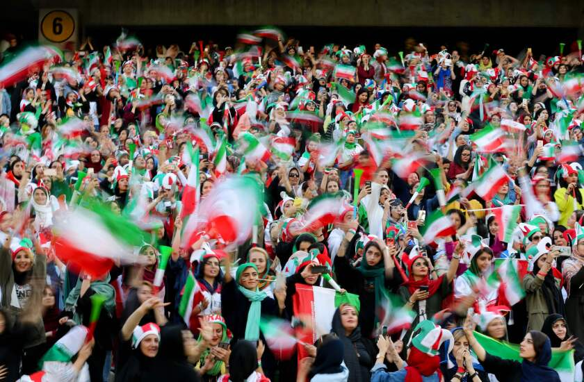 Iranian women cheer during the World Cup Qatar 2022 Group C qualification football match between Iran and Cambodia at the Azadi stadium in the capital Tehran on October 10, 2019. - The Islamic republic has barred female spectators from football and other stadiums for around 40 years, with clerics arguing they must be shielded from the masculine atmosphere and sight of semi-clad men. Women fans are attending the football match freely for the first time in decades, after FIFA threatened to suspend the country over its controversial male-only policy. (Photo by ATTA KENARE / AFP) (Photo by ATTA KENARE/AFP via Getty Images) ** OUTS - ELSENT, FPG, CM - OUTS * NM, PH, VA if sourced by CT, LA or MoD **