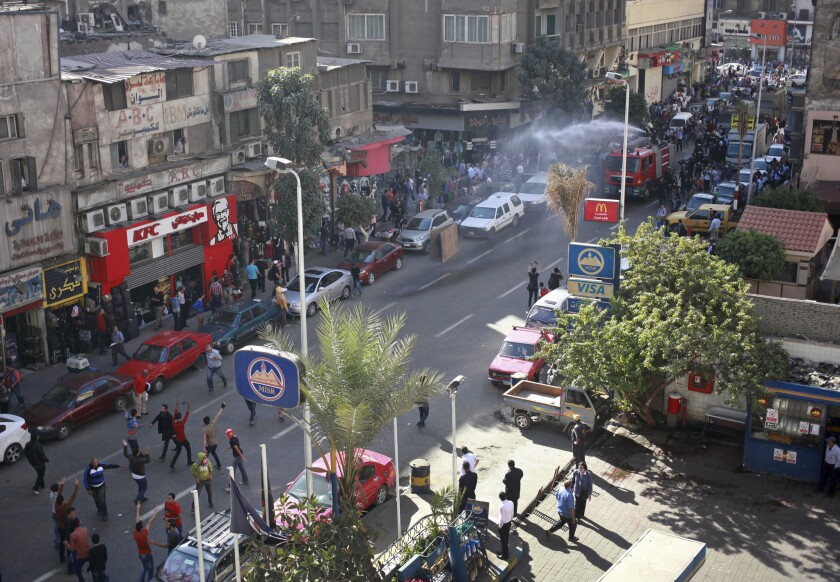 In downtown Cairo, police fire a water cannon to disperse a protest by dozens of activists commemorating the death of a protester a year earlier.