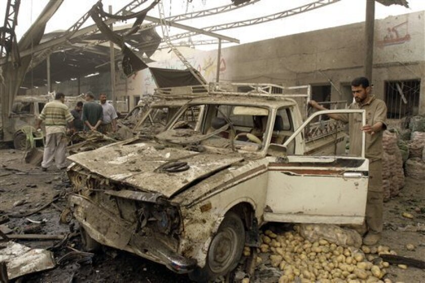 A man stands by a car destroyed in a car bomb explosion in Baghdad, Iraq, Wednesday, May 6, 2009. A car bomb exploded Wednesday at the entrance to a fruit and vegetable market in south Baghdad, killing 11 people and wounding about 30, police and hospital officials said. (AP Photo/Loay Hameed)