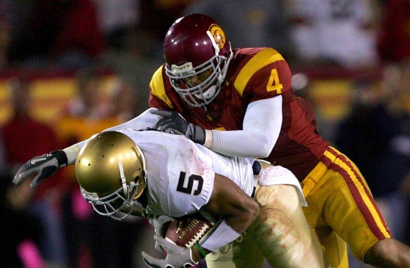 USC safety Kevin Ellison tackles Notre Dame receiver Rhema McKnight on Nov. 25, 2006, at the Coliseum.