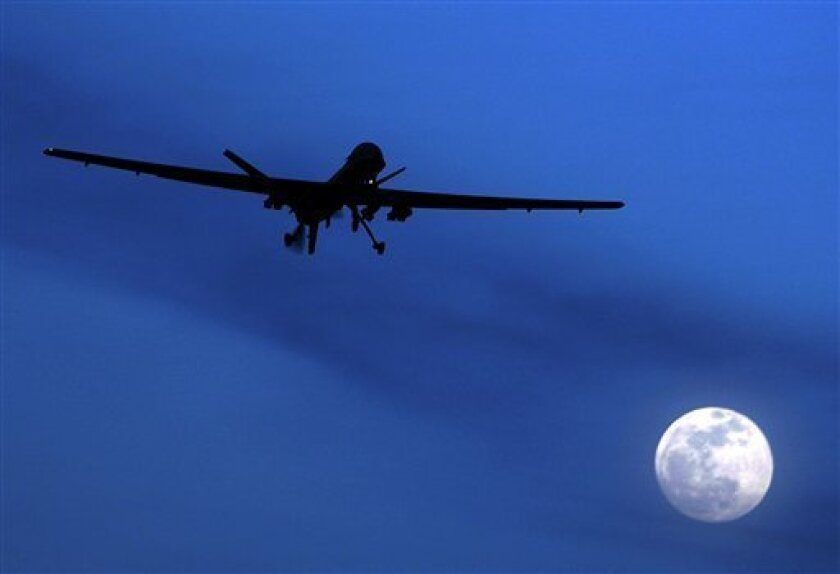 FILE - In this Jan. 31, 2010 file photo, a U.S. Predator drone flies over the moon above Kandahar Air Field, southern Afghanistan. The Taliban are moving fighters into Kandahar, planting bombs and plotting attacks as NATO and Afghan forces prepare for a summer showdown with insurgents, according to