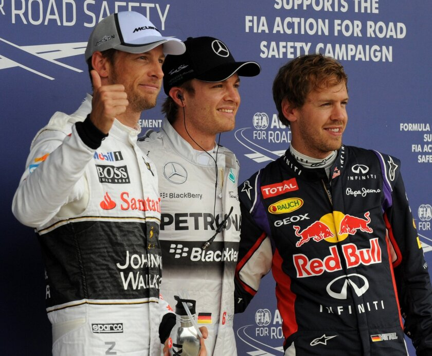 Germany's Nico Rosberg of Mercedes, centre, who won the pole position, Germany's Sebastian Vettel, right, of Red Bull, who finished second, and Britain's Jenson Button, left, of McLaren Mercedes who finished third, pose for the photographers following the qualifying session of the British Formula One Grand Prix at Silverstone circuit, Silverstone, England, Saturday, July 5, 2014. The British Formula One Grand Prix will be held on Sunday, July 6, 2014. (AP Photo/Rui Vieira)
