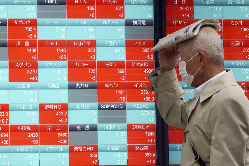 A man walks past an electronic board showing Japan's Nikkei 225 index in Tokyo on Monday.