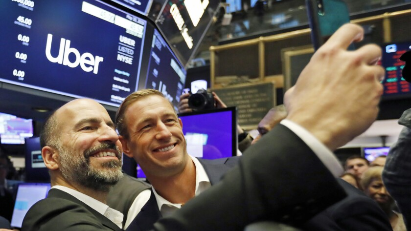 Uber CEO Dara Khosrowshahi, left, and Ryan Graves, a board member, pose for a photo before the compa