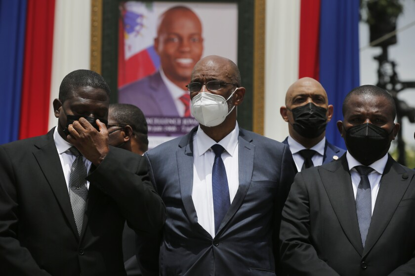 FILE - In this July 20, 2021 file photo, Haiti's designated Prime Minister Ariel Henry, center, and interim Prime Minister Claude Joseph, right, pose for a group photo with other authorities in front of a portrait of slain Haitian President Jovenel Moise at the National Pantheon Museum during a memorial service for Moise in Port-au-Prince, Haiti. Haiti's chief prosecutor has asked a judge to charge Henry in the slaying of his predecessor and barred him from leaving the country. (AP Photo/Joseph Odelyn, File)