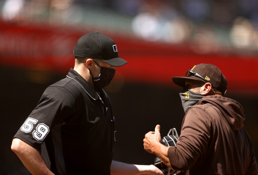 Padres manager Jayce Tingler talks with umpire Nic Lentz after being ejected