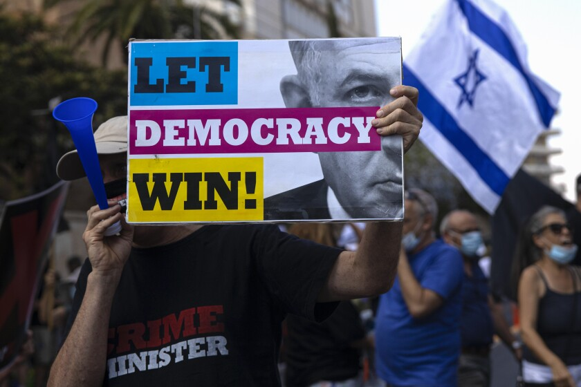 """An Israeli protester hold a sign during the """"Black Flag"""" protest against Israeli Prime Minister Benjamin Netanyahu in Jerusalem, Friday, July 10, 2020. Hundreds of Israelis protested outside Israel's Prime Minister Benjamin Netanyahu residency in Jerusalem demanding he resign his post because he is on trial for corruption charges. (AP Photo/Tsafrir Abayov)"""