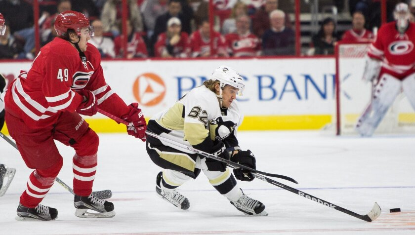 Pittsburgh Penguins' Carl Hagelin (62), of Sweden, fights for the puck against Carolina Hurricanes' Victor Rask (49), also of Sweden, during the second period of an NHL hockey game in Raleigh, N.C., Friday, Feb. 12, 2016. (AP Photo/Ben McKeown)