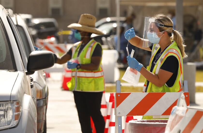 A worker demonstrates how to administer a coronavirus self-test to drivers in South Los Angeles.