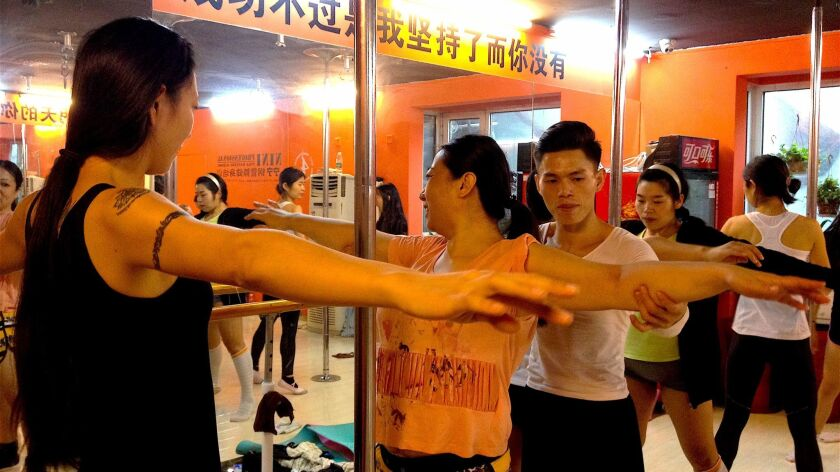 Hou Xing, holding a woman's arm, teaches a basic pole dancing technique course.