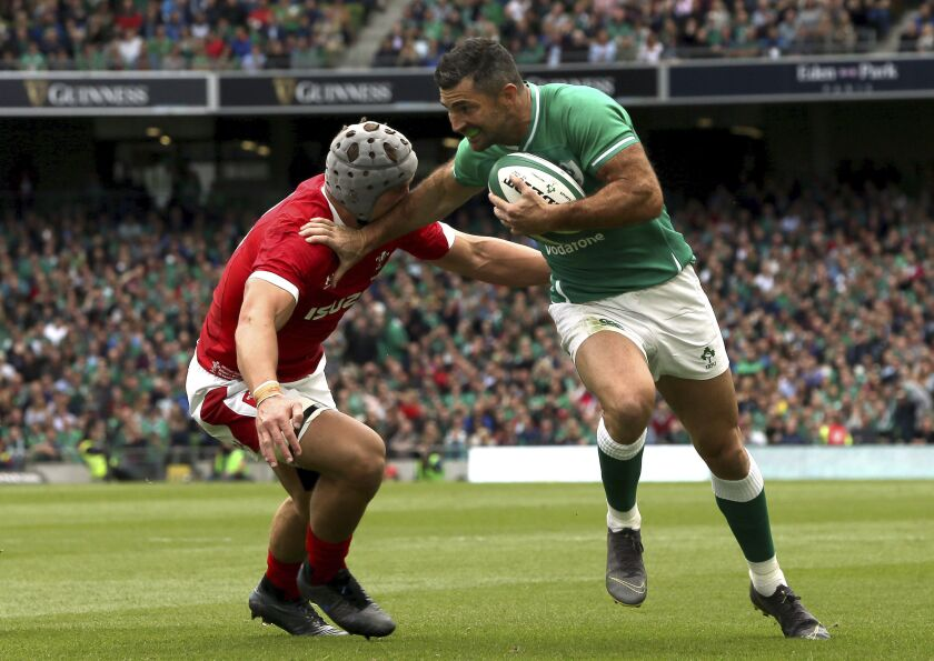 Ireland's Rob Kearney, right, passes Wales' Jonathan Davies on his way to scoring his sides fourth try during the summer series rugby match between Wales and Ireland at the Aviva Stadium, Dublin, Ireland, Saturday Sept. 7, 2019. (Brian Lawless/PA via AP)