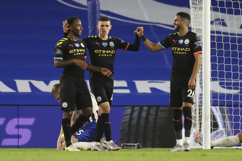 Manchester City's Raheem Sterling, left, celebrates after scoring his side's fifth goal during the English Premier League soccer match between Brighton and Manchester City at the Falmer stadium in Brighton, England, Saturday, July 11, 2020. (Cath Ivill/Pool via AP)