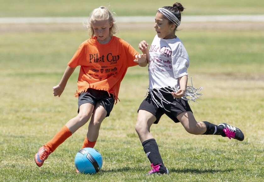 Davis Elementary's Savannah Roy, left, and Sonora Elementary's Caylin Caro battle for a ball during a girls' fifth- and sixth-grade Bronze Division quarterfinal match at the Daily Pilot Cup in Costa Mesa on June 2, 2018.