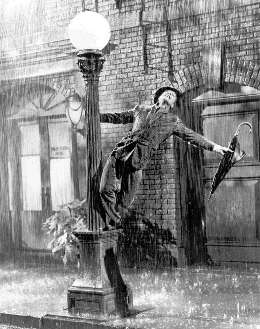 """FILE - In this undated file photo, Gene Kelly performs in the 1952 film """"Singin' in the Rain.""""  The grey wool  suit was purchased Thursday, Dec. 12, 2013,  by the theme restaurant Planet Hollywood International for more than $106,000. Kelly wore the suit for the soggy featured dance in the 1952 mov"""
