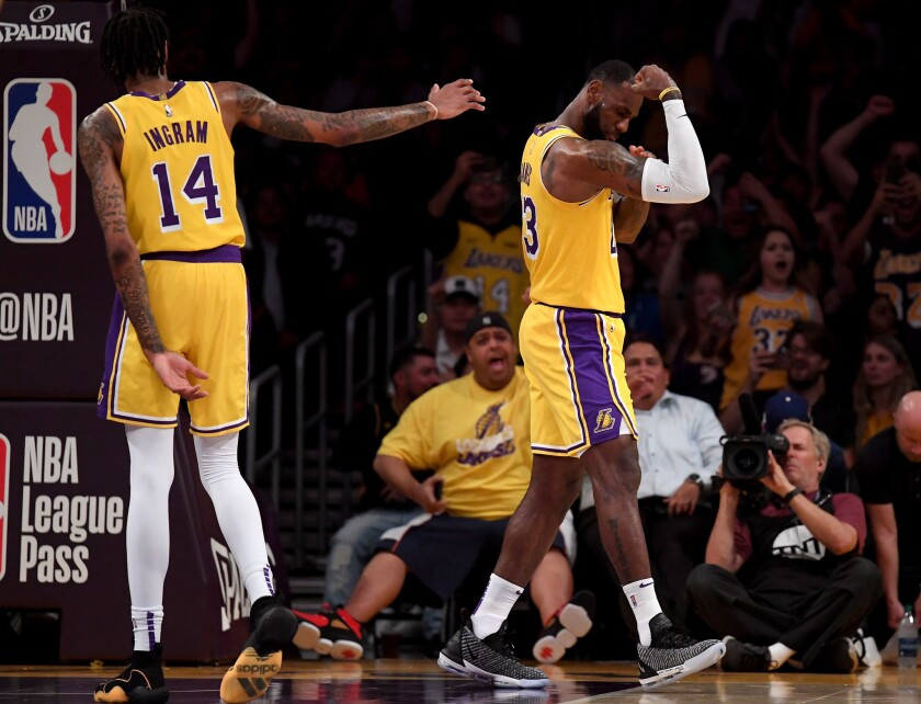 LeBron James #23 of the Los Angeles Lakers celebrates his dunk in front of Brandon Ingram #14 during a preseason game against the Denver Nuggets at Staples Center on October 2, 2018 in Los Angeles, California.