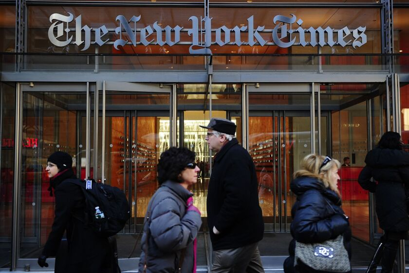 People walk by an entrance to the New York Times building