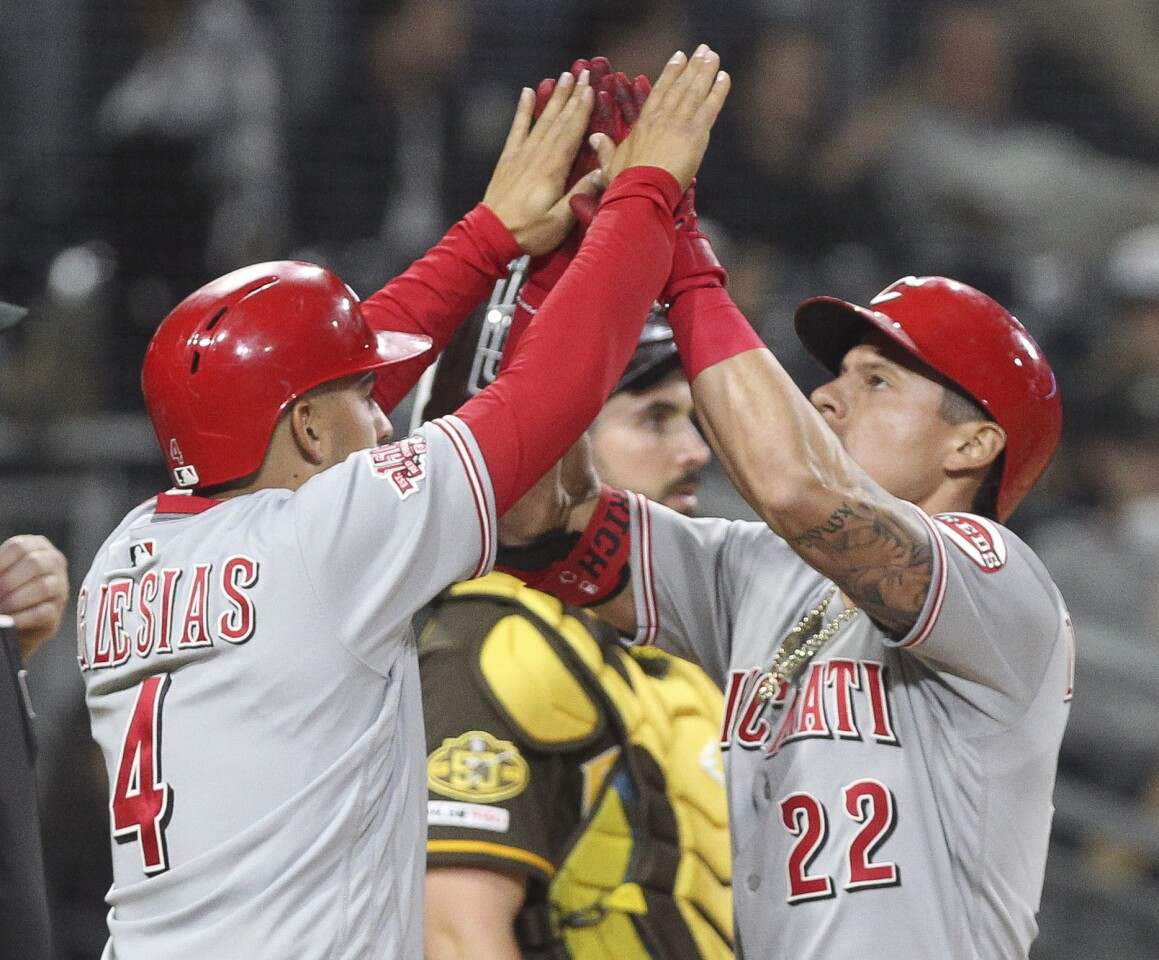 The Reds' Derek Dietrich, right, and Jose Iglesias celebrate Dietrich's two-run home run as Padres' catcher Austin Hedges stands nearby in the eleventh inning.