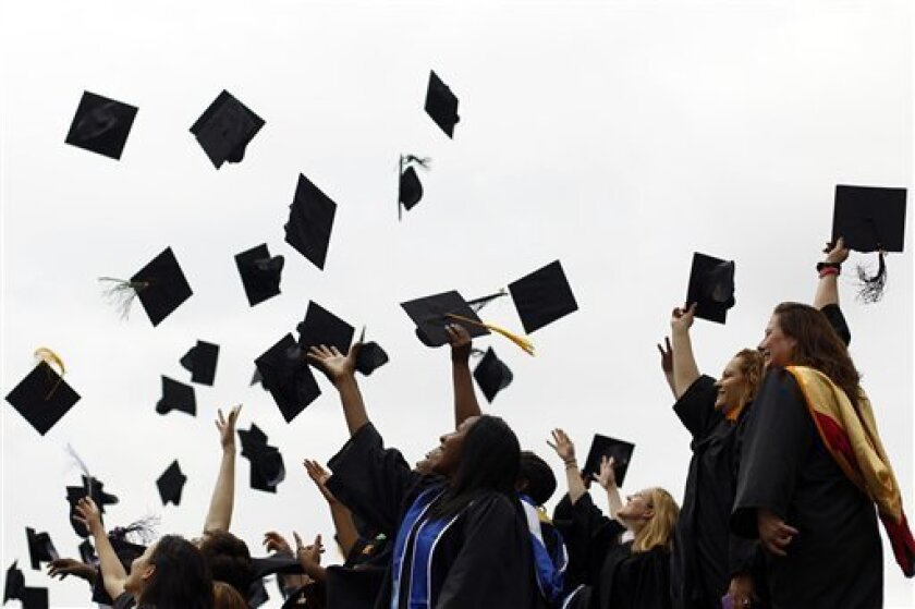 FILE-In this May 20, 2011, file photo, graduates from various institutions toss their hats in the air in Philadelphia. Many graduatues are burried in student loans, but Joe Mihalic, a  business school graduate paid off $90k in student loans in 7 months and blogged about his experience at NoMoreHarv
