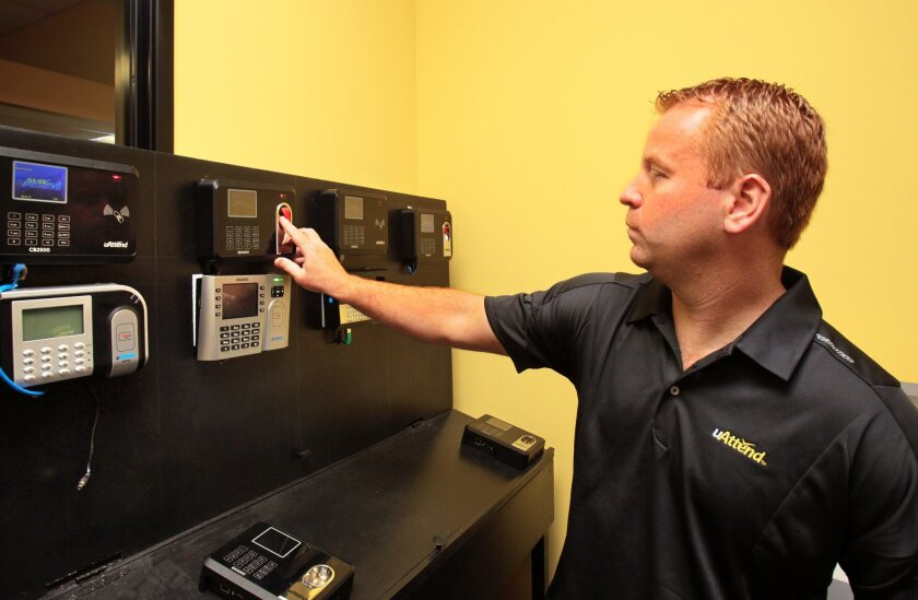 Chad Buckmaster, CEO of ProccessingPoint, uses one of his company's fingerprint biometric time clock devices.