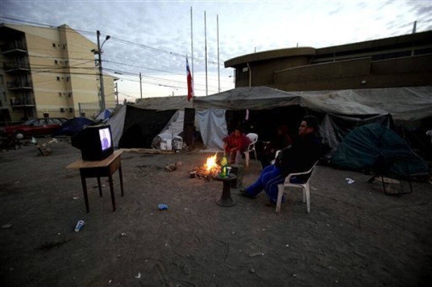 People watch TV outside their quake-damaged houses in Concepcion, Chile, Saturday, March 6, 2010. An 8.8-magnitude earthquake struck central Chile last Feb. 27, causing widespread damage.(AP Photo/ Natacha Pisarenko)