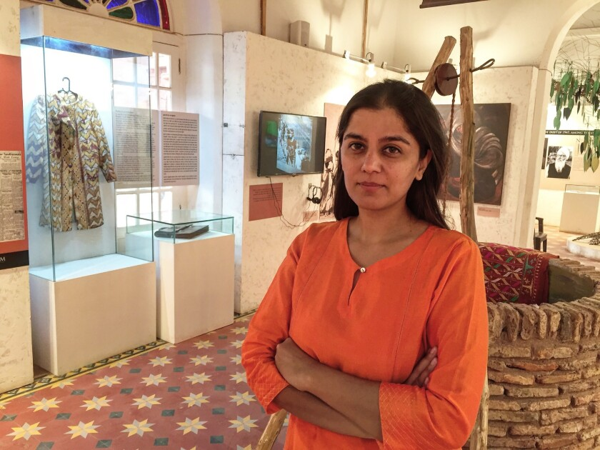 Trustee Mallika Ahluwalia is pictured in one room of the Partition Museum. Displayed at left are a coat and briefcase donated by survivors.